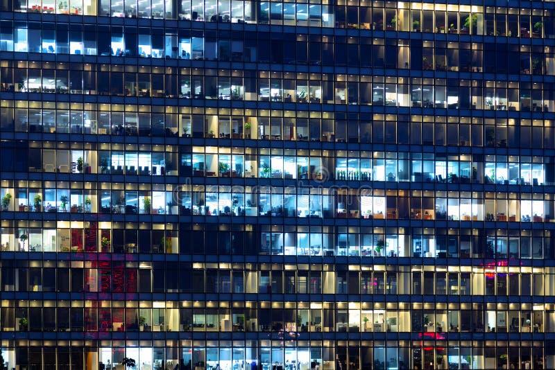 Kontorsbyggnadyttersida i den sena aftonen med inre ljus Affärsfolk som arbetar i aftonen Upplyst kontor royaltyfri fotografi