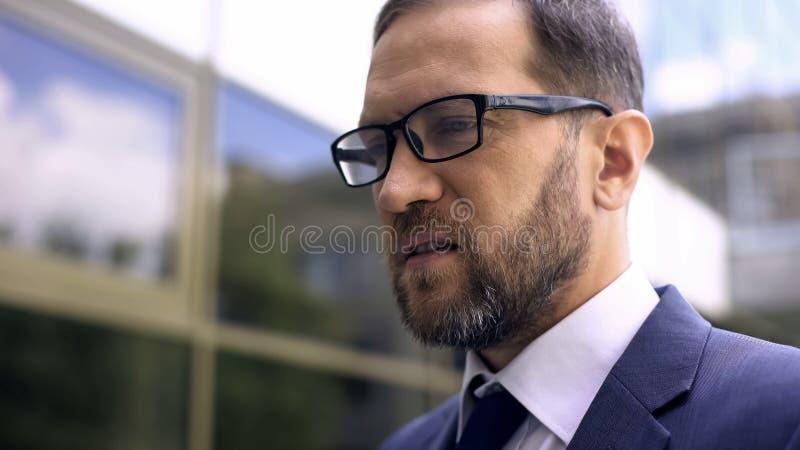 Kontorschefen i glasögon tätt upp, oroade om affärsproblem, arbete royaltyfri bild