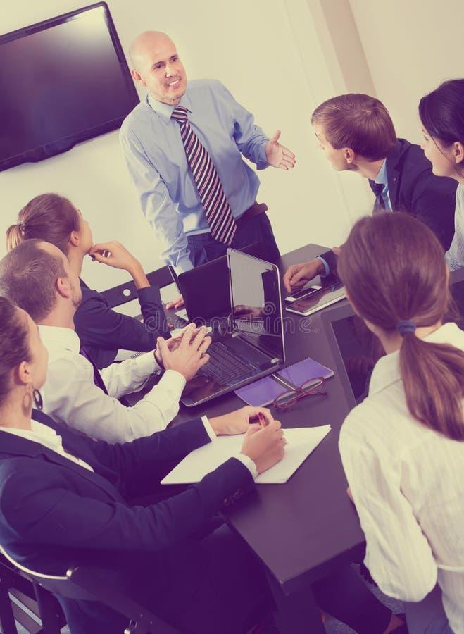 Kontorschefer som talar om affärsprojekt royaltyfri bild