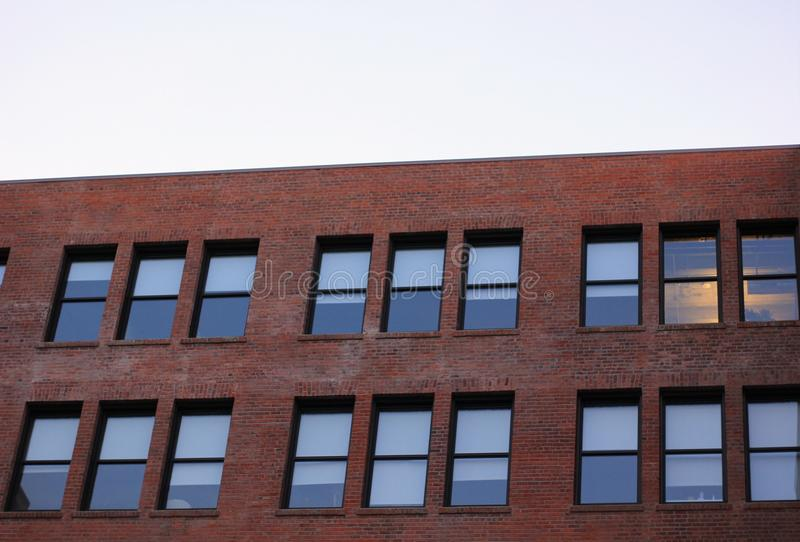 Kontorsfönster på en tegelstenbyggnad royaltyfri foto