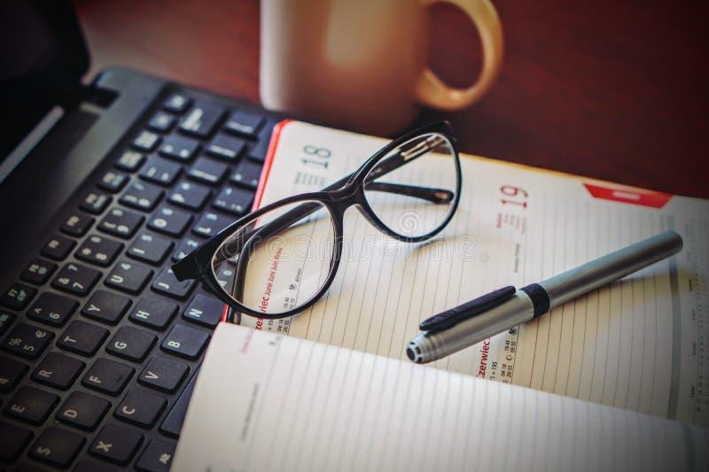 Kontorskalender med exponeringsglas och pennan royaltyfria bilder