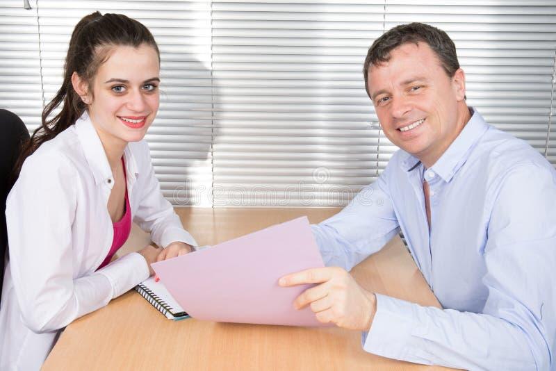 Kontorskollegor ser tillsammans en funktionsduglig mapp på kontorsskrivbordet royaltyfri bild