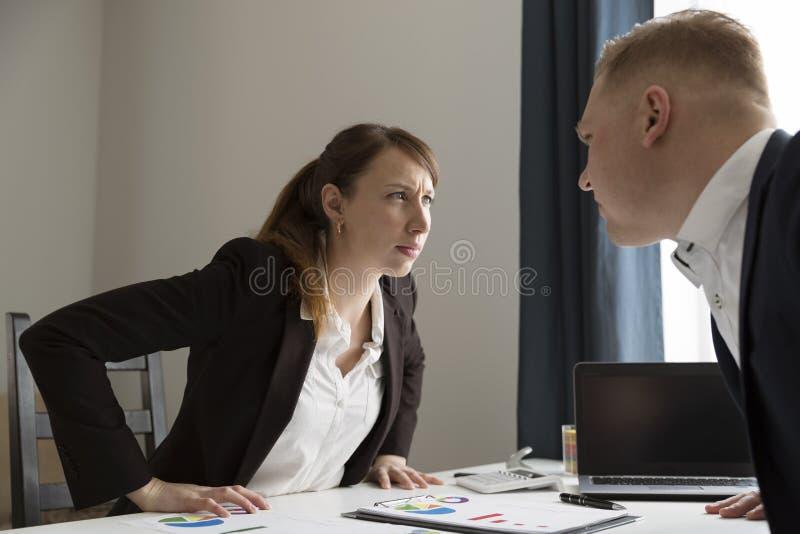 Kontorskonflikt mellan mannen och kvinnan Konkurrens mellan män a arkivfoto