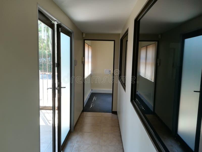 Kontorskorridor eller passage med tonade fönster på sidan arkivbilder