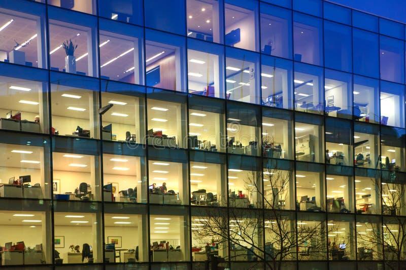 Kontorskvarter med massor av tända upp fönster och sena kontorsarbetare inom Stad av den London affärsarian i skymning royaltyfria foton