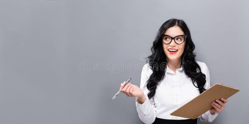 Kontorskvinna med en skrivplatta royaltyfri bild