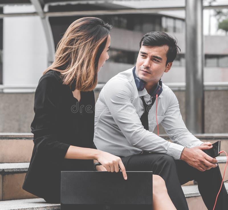 Kontorskvinna med par för affärsman som talar flörta utomhus- sammanträde royaltyfri foto