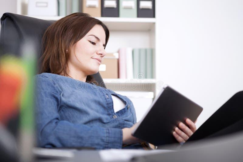 Kontorskvinna som kopplar av på hennes stol med minnestavlan arkivbild