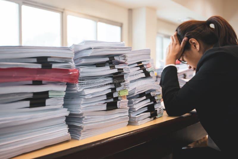 Kontorskvinnaarbetaren bedrövas med mycket skrivbordsarbete på hennes skrivbord royaltyfria bilder