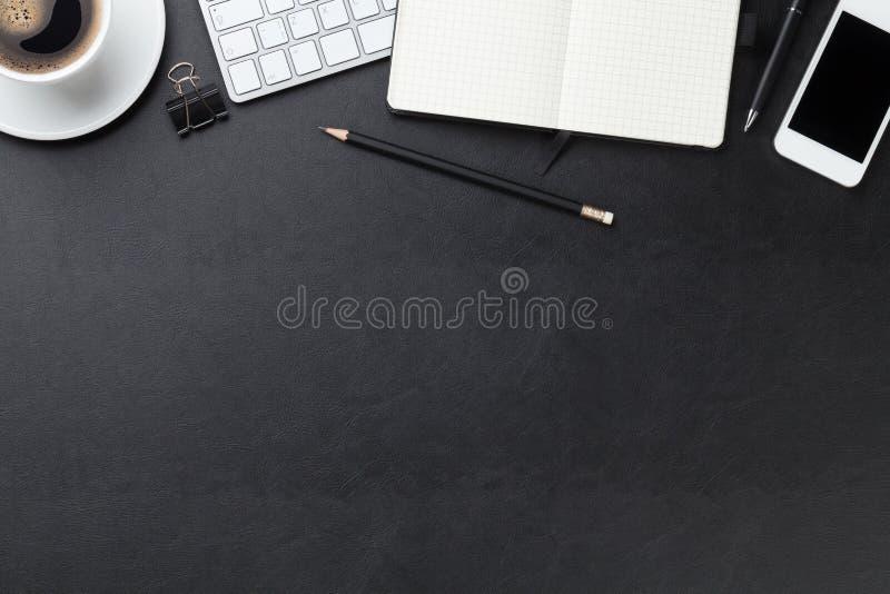 Kontorsläderskrivbord med datoren, tillförsel och kaffe fotografering för bildbyråer
