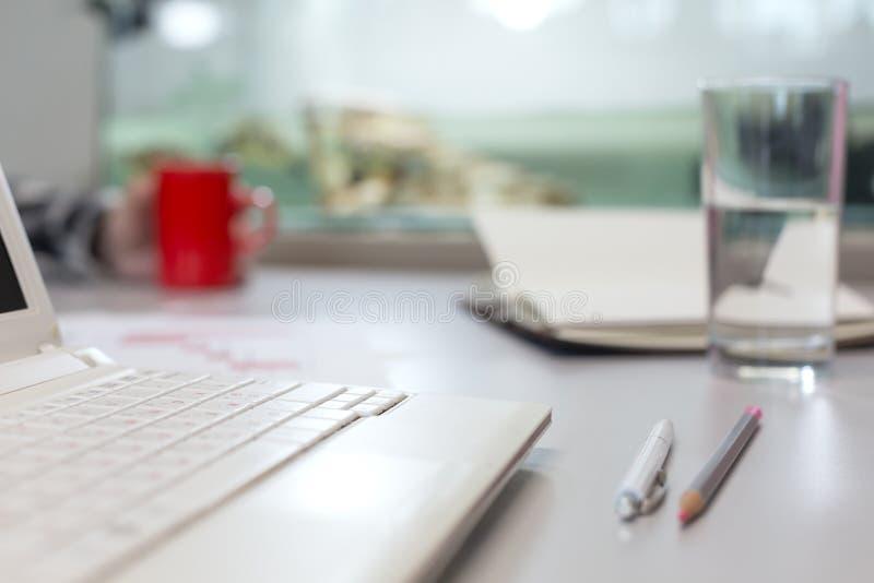 Kontorslivbegrepp - datorexponeringsglas av vatten och brevpapper royaltyfri foto