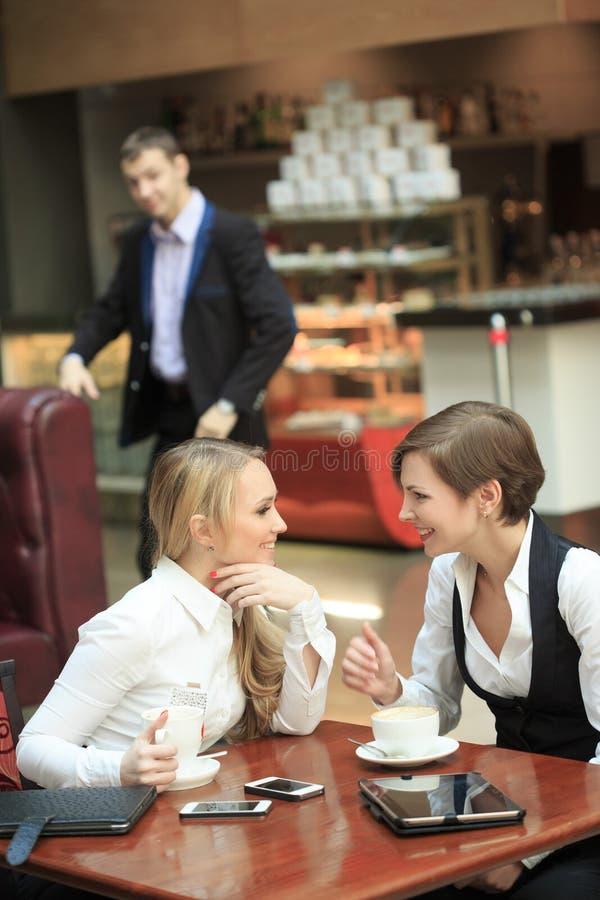 Kontorspersonal för två flickvänner i kafé på a royaltyfria bilder
