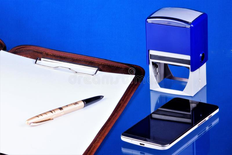Kontorsredovisningsskrivbord, blå bakgrund, med den nödvändiga tillbehören Mapp med dokument, smartphonemeddelare för arkivbild