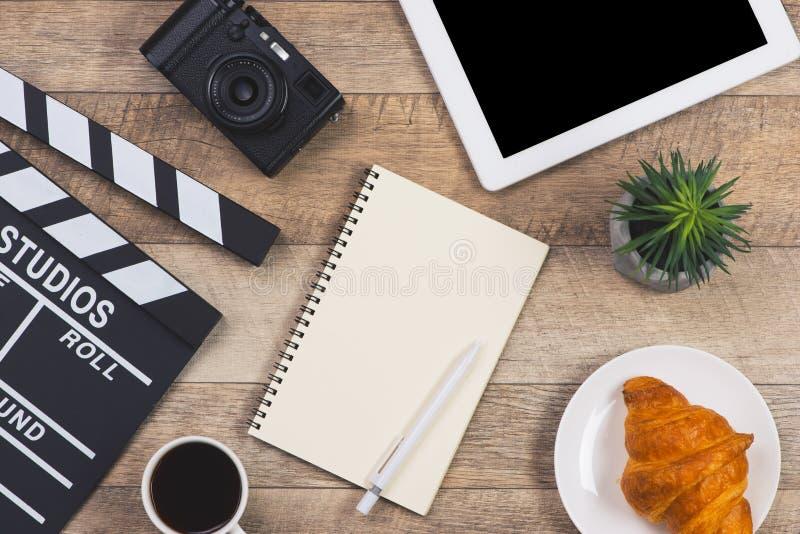 Kontorssaker med filmclapperen, digital tabell, kaffekopp, penna arkivbild
