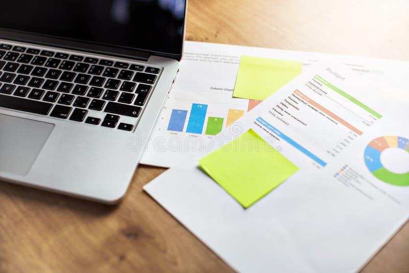 Kontorsskrivbord, bärbar dator och legitimationshandlingar med budgetkolonn- och cirkeldiagram arkivbilder