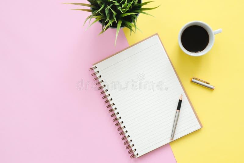 Kontorsskrivbord för bästa sikt med åtlöje upp anteckningsböcker, växten, kaffekoppen och kopieringsutrymme på bakgrund för paste arkivfoto