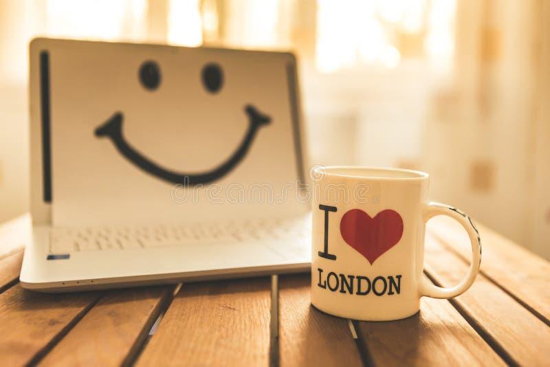 Kontorsskrivbord med datoren; kaffekopp och leende arkivfoton
