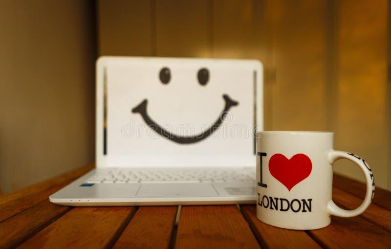 Kontorsskrivbord med datoren; kaffekopp och leende royaltyfria foton