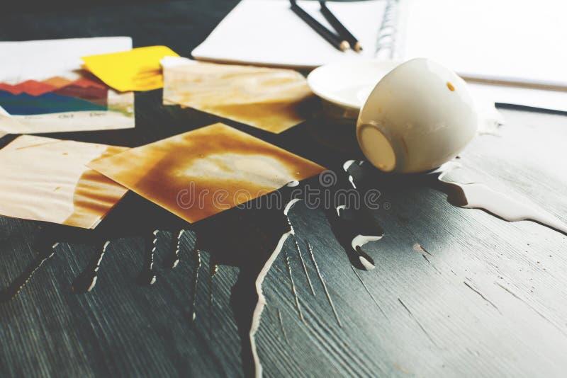 Kontorsskrivbord med den spillda kaffecloseupen royaltyfri fotografi
