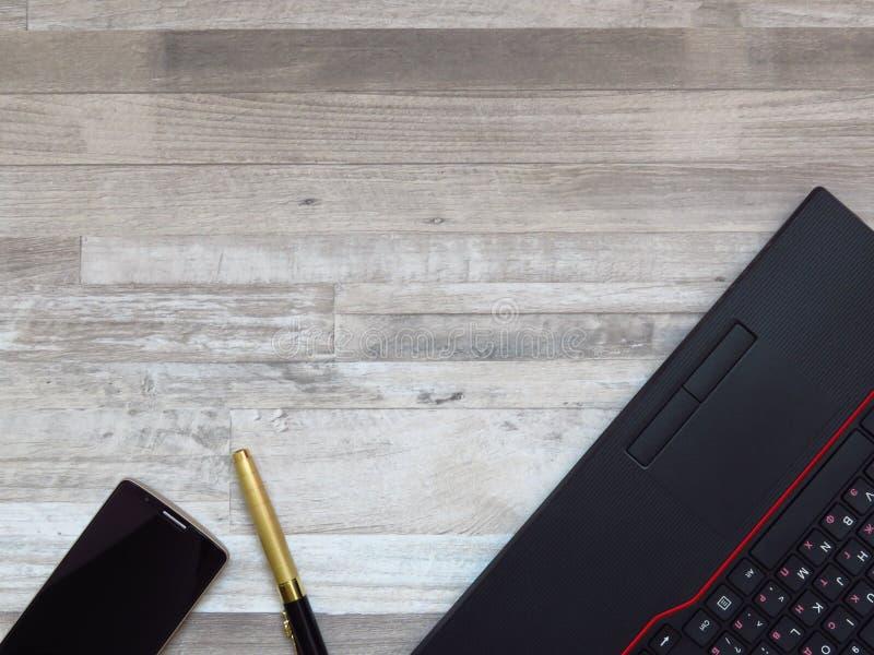 Kontorsskrivbord med den svarta bärbara datorn, guld- färgmobiltelefon, guld- lyxig penna på vit wood texturbakgrund arkivfoto