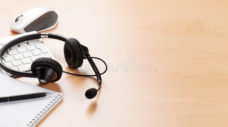 Kontorsskrivbord med hörlurar med mikrofon Service för appellmitt royaltyfria foton