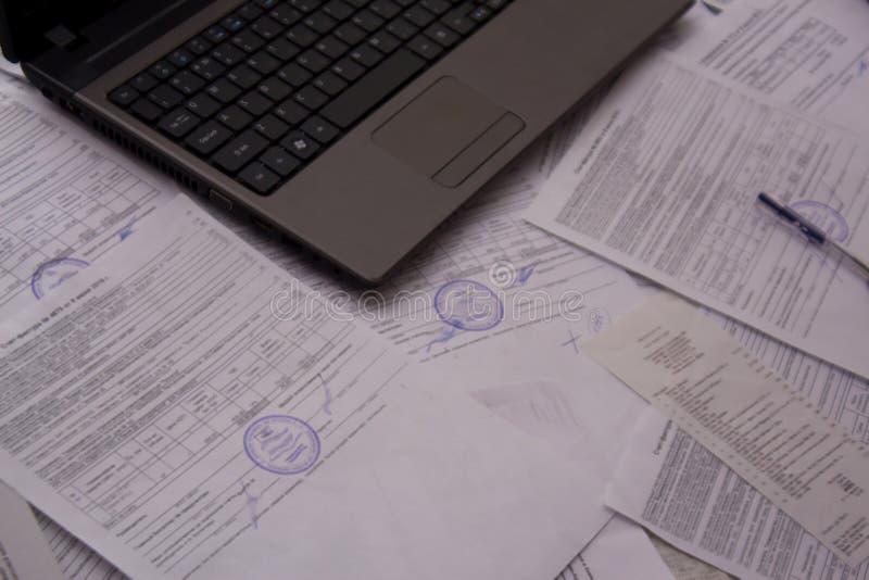 Kontorsskrivbord med legitimationshandlingar, kvitton och dokument Arbete med dokument på växten eller företaget Bärbar dator ell arkivbilder
