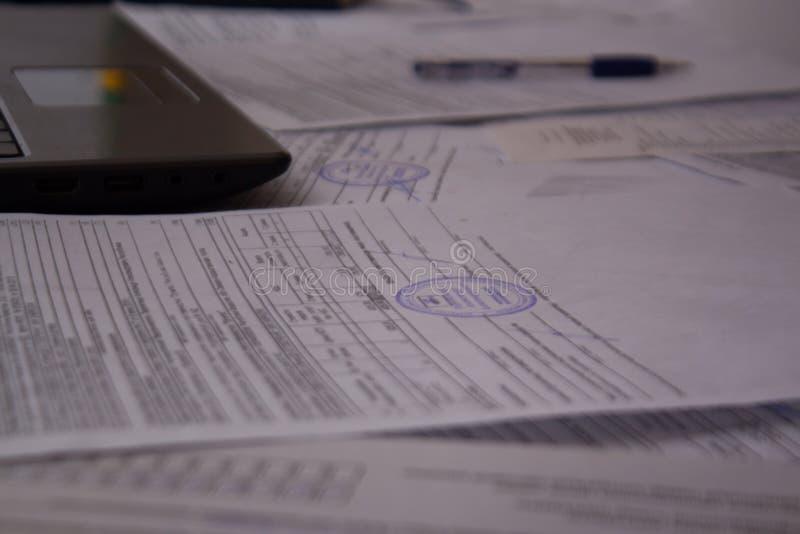 Kontorsskrivbord med legitimationshandlingar, kvitton och dokument Arbete med dokument p? v?xten eller f?retaget B?rbar dator ell arkivfoto