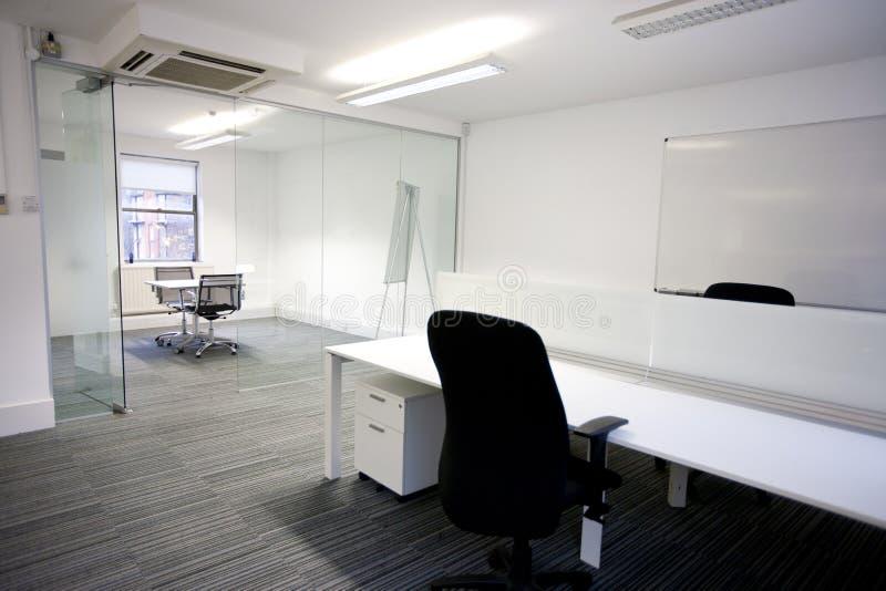 Kontorsskrivbord med mötesrum i bakgrund royaltyfri foto