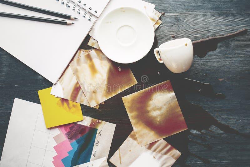 Kontorsskrivbord med spillt kaffe arkivbild
