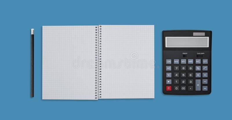 Kontorsskrivbord och affärsidé Tom spiralanteckningsbok, räknemaskin och blyertspenna som isoleras över blå bckground Worklplace  arkivfoton
