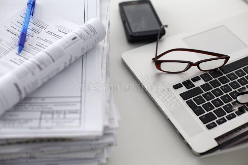 Kontorsskrivbord som en bunt av rapporter för datorpapper arbetar arkivfoton