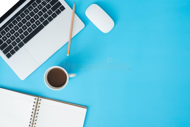 Kontorsskrivbordet för den bästa sikten med bärbara datorn, anteckningsböcker och kaffekoppen på blått färgar bakgrund Bästa sikt arkivbilder
