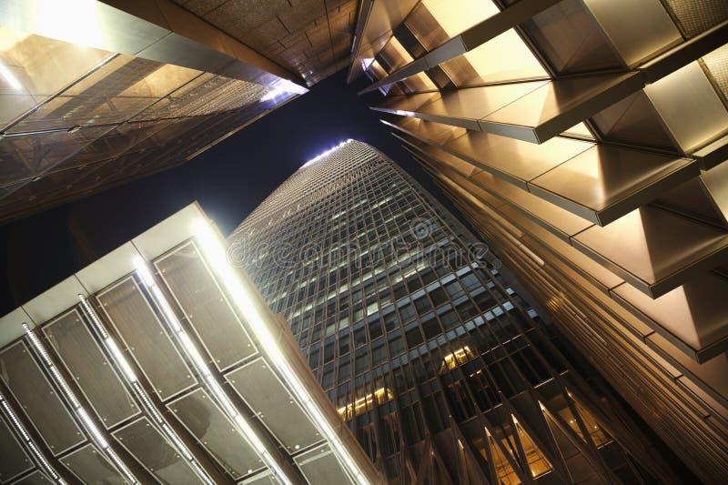 Kontorsskyskrapa, direkt under, nattetid royaltyfri bild