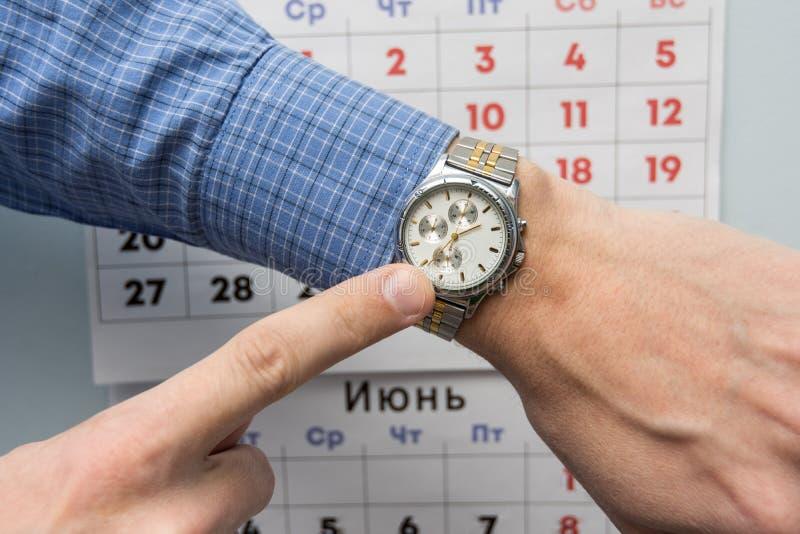 Kontorsspecialister räcker punkter till ett armbandsur, i bakgrunden är en väggkalender fotografering för bildbyråer