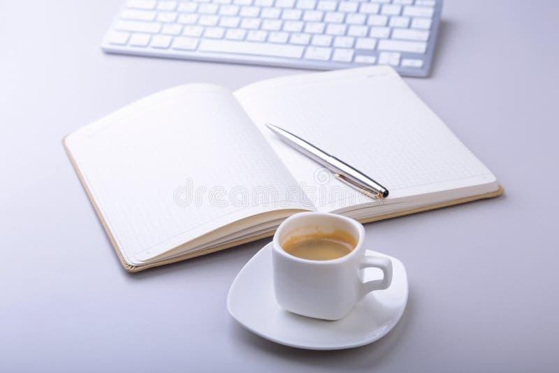 Kontorstabell med anteckningsboken, kulspetspenna, datortangentbord, kopp kaffe, minnestavlaPC kopiera avstånd royaltyfri fotografi