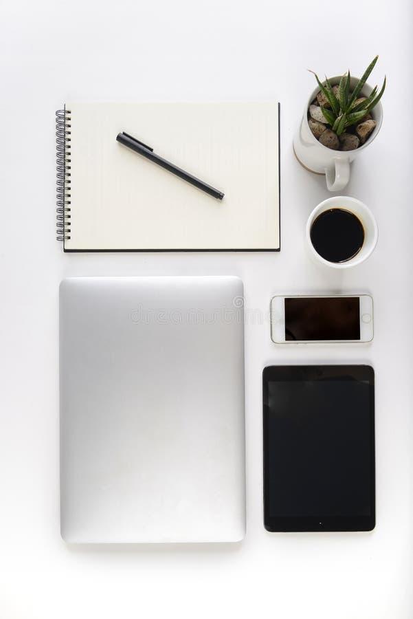 Kontorstabell med bärbar datordatoren, anteckningsboken, den digitala minnestavlan och smartphonen på vit bakgrund fotografering för bildbyråer