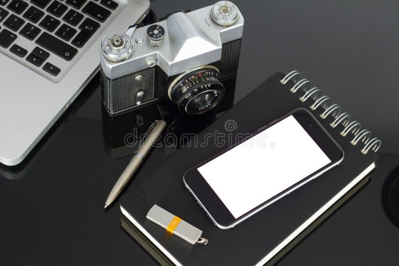 Kontorstabell med bärbara datorn, telefonen och tillförsel royaltyfria bilder