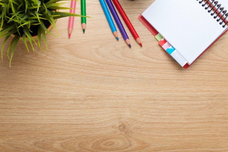 Kontorstabell med blomman, den tomma notepaden och färgrika blyertspennor royaltyfri foto