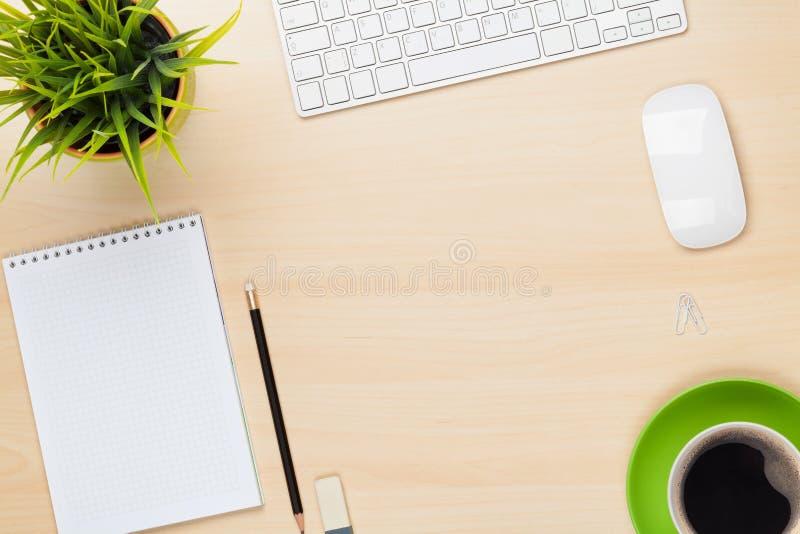 Kontorstabell med den notepad-, dator-, blomma- och kaffekoppen arkivfoton