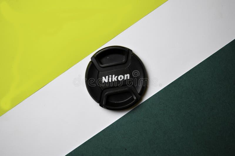 Kontorstabell med det Nikon Lens locket på färgbakgrund royaltyfria bilder