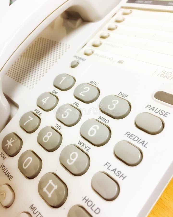 Kontorstelefon, grått tangentbord i den vita klassiska telefonen Denna är en apparat för att tjänstemannen ska kontakta med andra arkivfoton