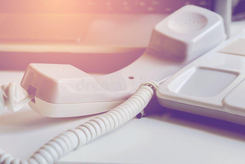 Kontorstelefon, telefontelefonlur av kroken på skrivbordet arkivfoton