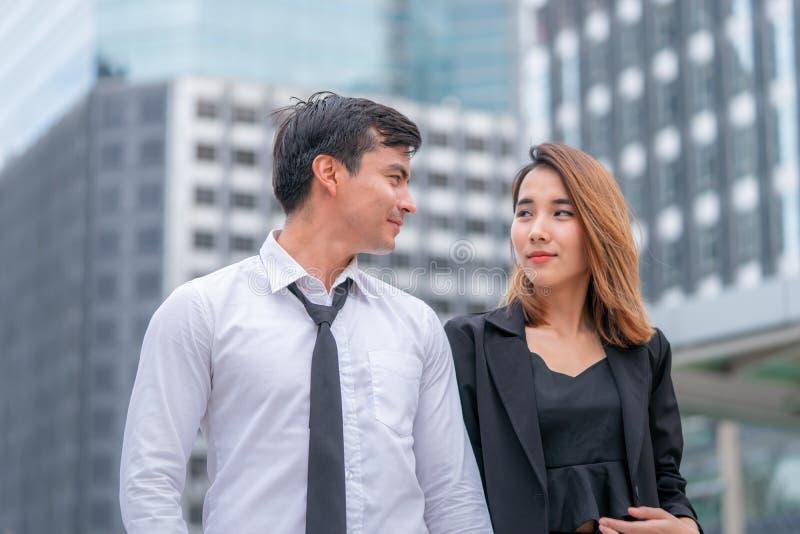Kontorsvänpar som tillsammans går i en modern stadsdrevstation royaltyfria foton