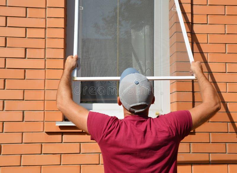 Kontrahent instaluje komara drucianego ekran na domowym okno ochraniać od insektów Komara drucianego ekranu instalacja zdjęcie stock