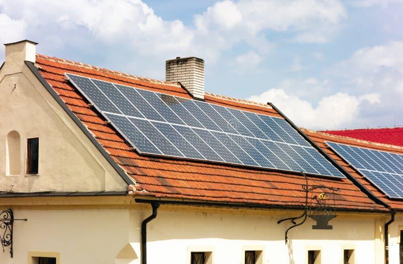 Kontrast des alten Hauses und der modernen Technologie, wie sie Solardach benutzt lizenzfreies stockbild