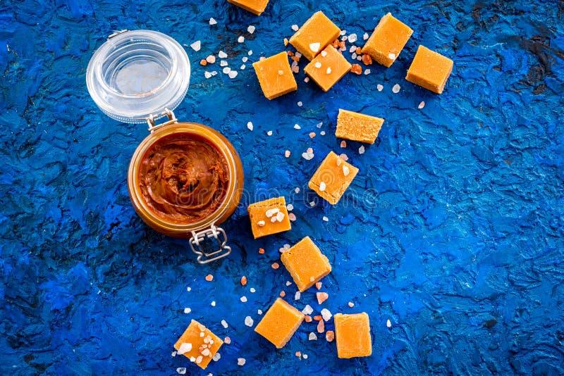 Kontrast von Aromen Die Kombination von salzigem und von süßem Karamellsoße im Glasgefäß nahe Karamellwürfeln auf Blau stockfotos