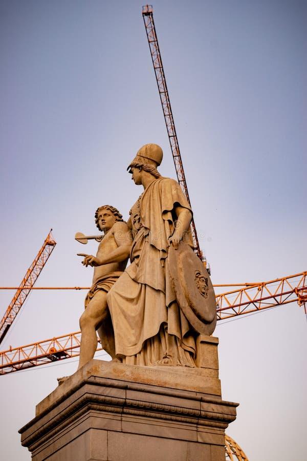 Kontrast zwischen alten griechischen Statuen und modernen Kränen in Berlin stockbild
