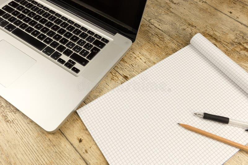 Kontrast zwischen alter und neuer Büroarbeit: geschossen von der Spitze eines Aluminiumlaptops auf einem hölzernen Schreibtisch m stockfoto