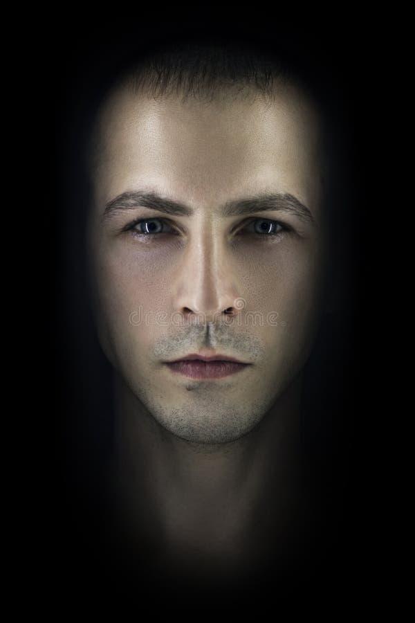 Kontrastera den manliga ståenden på svart bakgrund Tänd och skugga på framsidan för man` s Stilfull brutal man, konstfoto Konturf royaltyfria foton