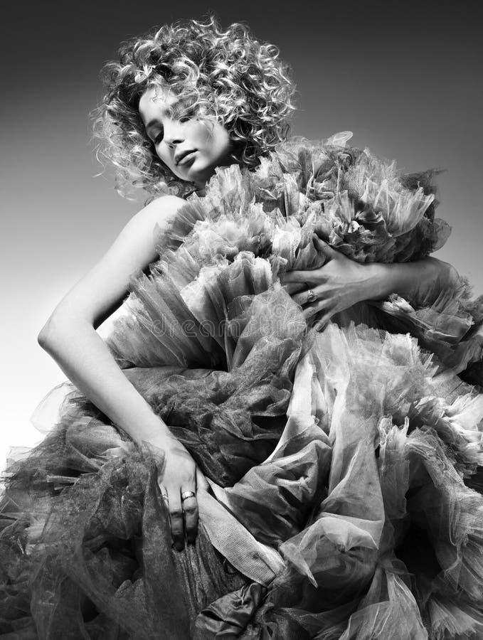 Kontrastierendes Schwarzweiss-Modeporträt der schönen jungen Frau, die in einem geschwollenen Kleid aufwirft lizenzfreie stockfotografie